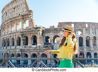 Woman standing near Colosseum in Rome listening to music -...