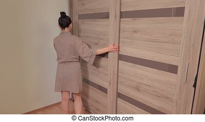 Woman standing near her wardrobe and close the door