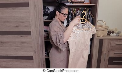 Woman standing near her wardrobe and holding dress
