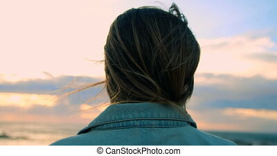 Woman standing near railings at beach 4k - Close-up of woman...