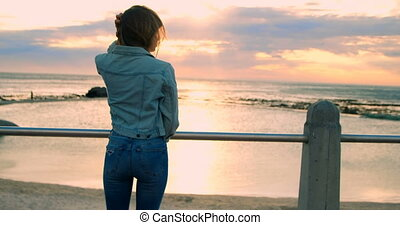Woman standing near railings at beach 4k - Young woman...