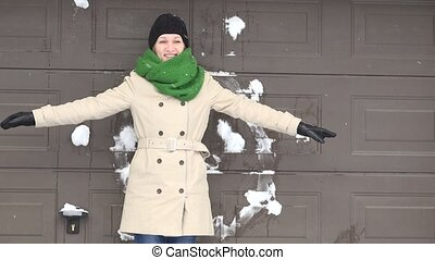 Woman standing near wall and someone throwing snow balls at her