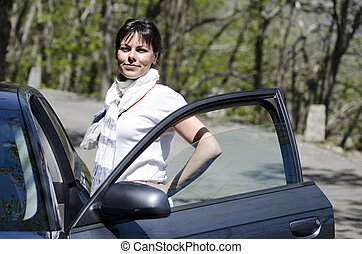 Woman standing next to a car