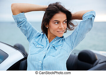 Woman standing next to her new car at the seaside