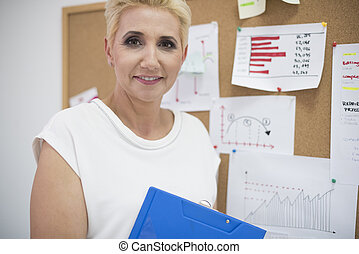 Woman standing next to the cork board