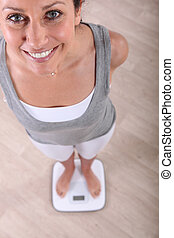 Woman standing on a pair of scales
