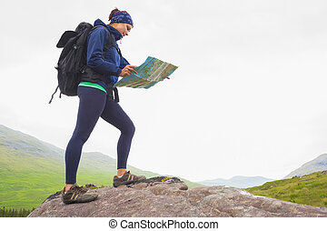 Woman standing on a rock reading map