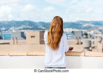 Woman standing on a roof terrace