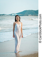 Woman standing on beach in summer. Happy multiracial Asian girl going to sea.