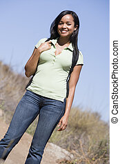 Woman standing on beach path smiling