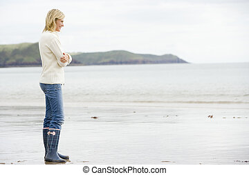 Woman standing on beach smiling