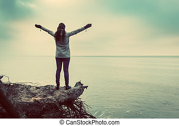 Woman standing on broken tree on wild beach with arms raised...