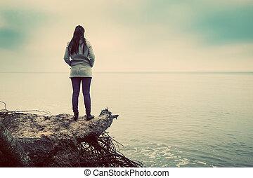 Woman standing on broken tree on wild beach looking at sea horizon