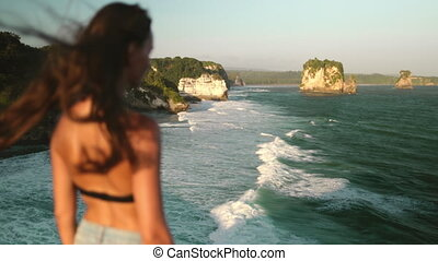 woman standing on cliff edge windy banawa beach - Woman ...