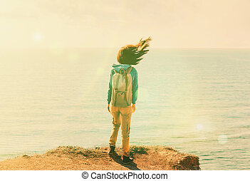 Traveler young woman with backpack standing on coastline near the sea in windy weather, her hair fluttering in the wind. Image with sunlight effect.