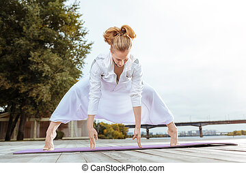 Woman standing on her toes while performing yoga pose -...