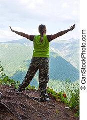 woman standing on mountain peak