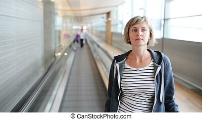 Woman standing on moving walkway in airport