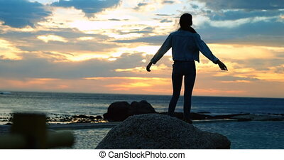 Woman standing on rock at beach 4k - Rear view of woman...