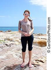 Woman standing on rocks at Beach of Kommetjie
