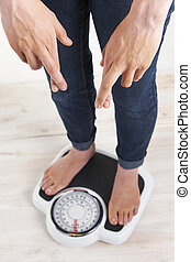 Woman Standing On Scales With Fingerrs Crossed