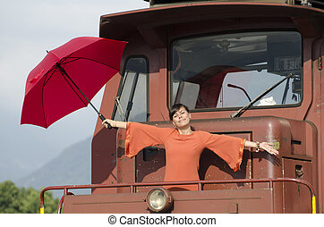 Woman standing on train with a red umbrella