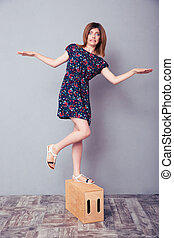 Woman standing on wooden box