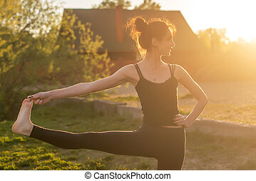 woman standing outdoors meditating in yoga position.