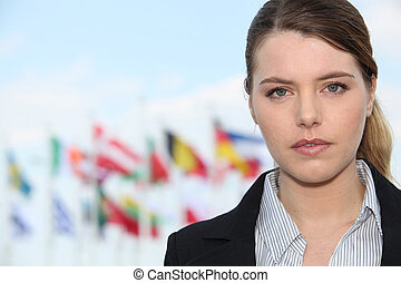 Woman standing outside flags in background