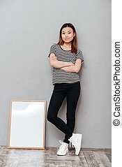 Woman standing over grey wall near copyspace blank.
