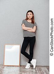 Woman standing over grey wall near copyspace blank.