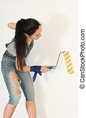 Woman standing painting a wall