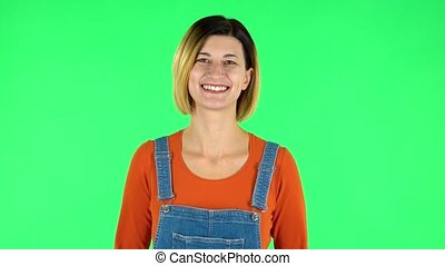 Woman standing, spreads out in a smile and looks at the camera. Green screen