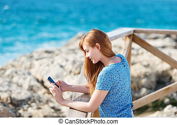 Woman standing texting on her mobile