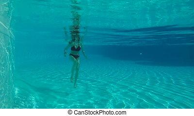 Woman standing underwater in slow motion