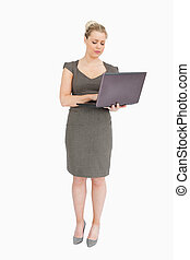 Woman standing while holding a laptop