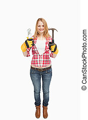 Woman standing while holding tools