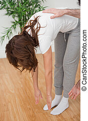 Woman standing while touching her feet with her hands in a...