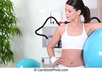 Woman standing with an exercise ball at the gym