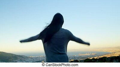 Woman standing with arms outstretched on top of the mountain...