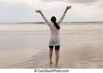 Woman standing with arms up on the beach