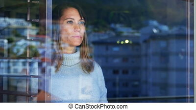 Woman standing with coffee cup near window 4k - Woman...