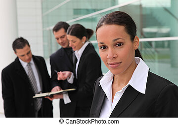 Woman standing with colleagues in front of an office building