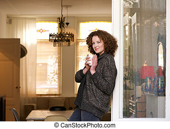 Woman standing with cup of tea at home