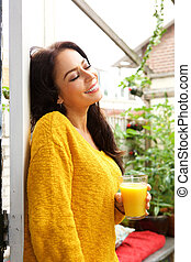 Woman standing with eyes closed with orange juice