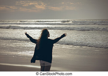 Woman standing with open arms at beach