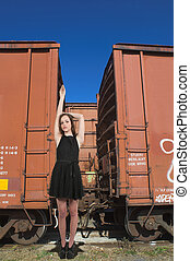 Woman Standing with Railroad Boxcars - Beautiful teenage...