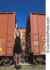 Woman Standing with Railroad Boxcars - Beautiful teenage...