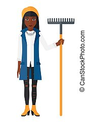 Woman standing with rake.