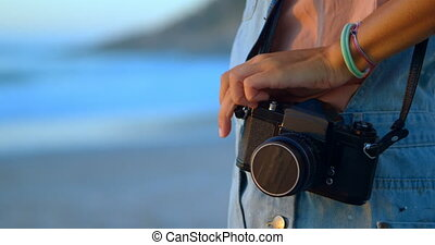 Woman standing with vintage camera inn the beach 4k - Mid...